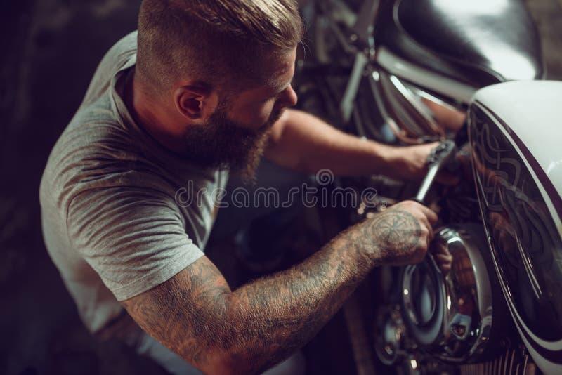 Uomo barbuto bello riparare il vostro motociclo nel garage fotografie stock libere da diritti