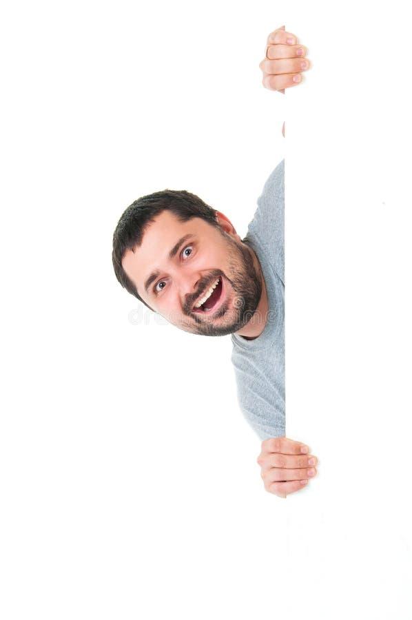 Uomo barbuto bello sorridente che porta una maglietta blu grigia e che posa dietro un pannello bianco isolato su fondo bianco Pos fotografie stock