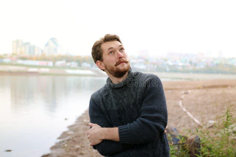 Uomo barbuto bello sui precedenti del fiume fotografie stock