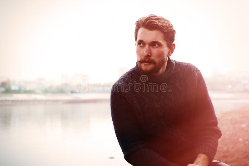Uomo barbuto bello sui precedenti del fiume immagine stock