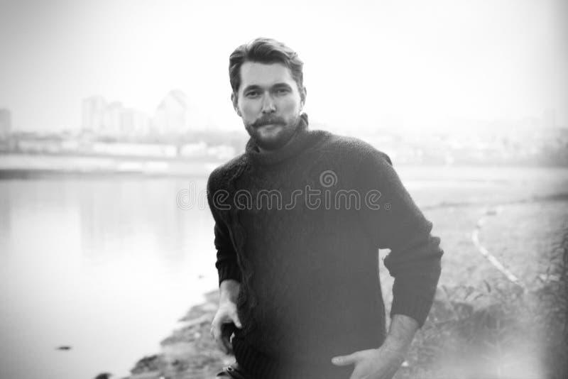 Uomo barbuto bello sui precedenti del fiume fotografia stock