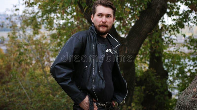 Uomo barbuto in bomber neri in una foresta immagini stock
