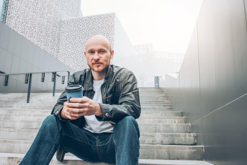 Uomo barbuto calvo adulto con la tazza di carta del caffè che si siede in scala alla via della città e che esamina macchina fotog fotografia stock libera da diritti
