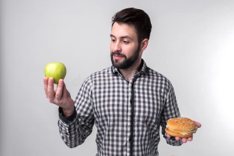 Uomo barbuto in camicia a quadretti su un fondo leggero che tiene un hamburger e una mela Il tipo opera la scelta fra veloce fotografia stock libera da diritti