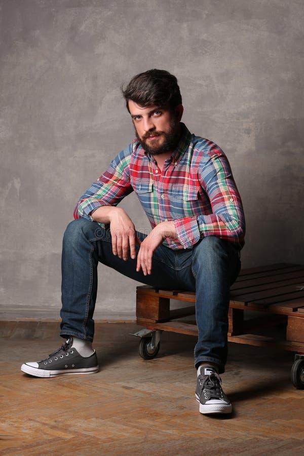 Uomo barbuto in camicia variopinta che si siede su una piattaforma fotografia stock