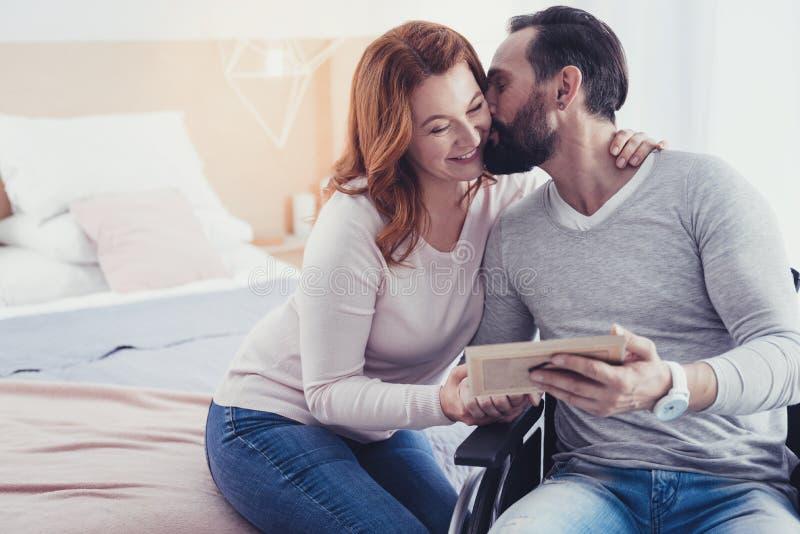 Uomo barbuto che bacia la sua moglie mentre sedendosi in una sedia a rotelle fotografia stock libera da diritti