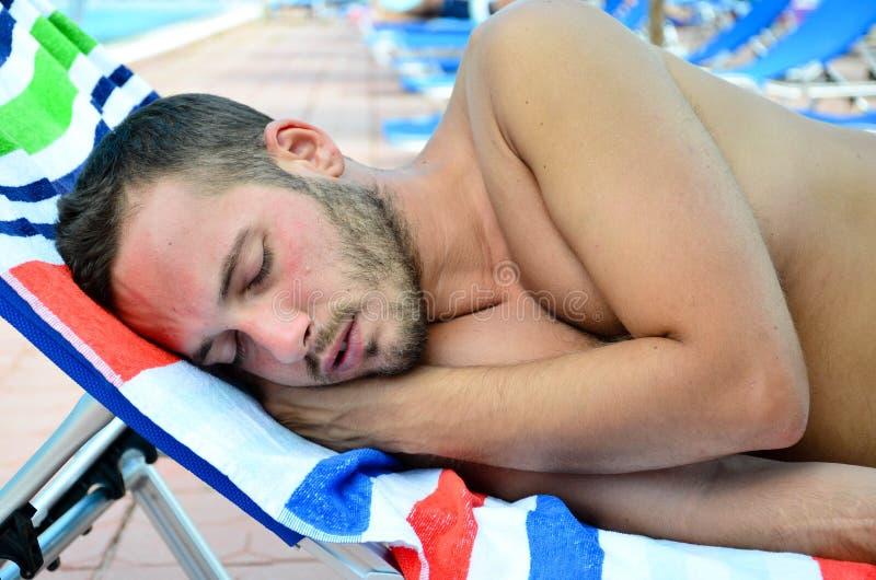 Uomo barbuto che dorme alla spiaggia fotografia stock libera da diritti