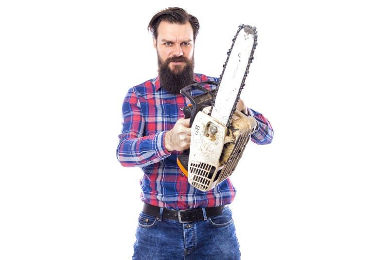Uomo barbuto che giudica una motosega isolata su un fondo bianco immagini stock libere da diritti