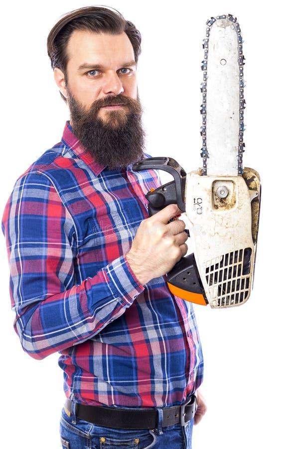 Uomo barbuto che giudica una motosega isolata su un fondo bianco immagine stock libera da diritti