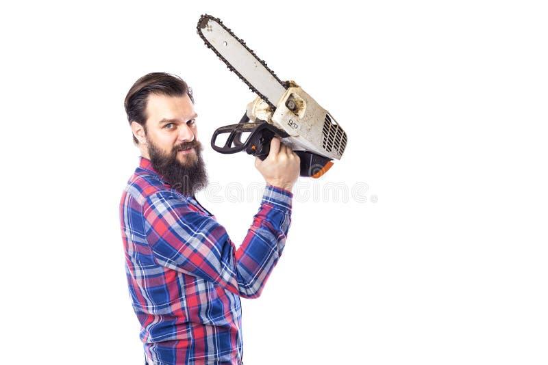 Uomo barbuto che giudica una motosega isolata su un fondo bianco immagini stock