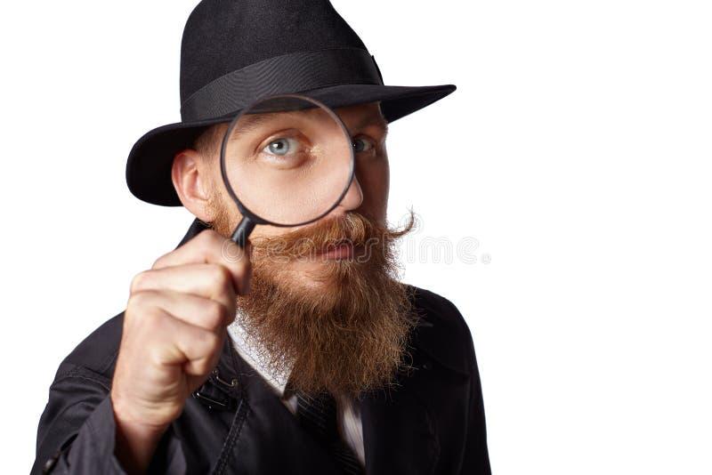 Uomo barbuto che guarda tramite una lente d'ingrandimento immagine stock