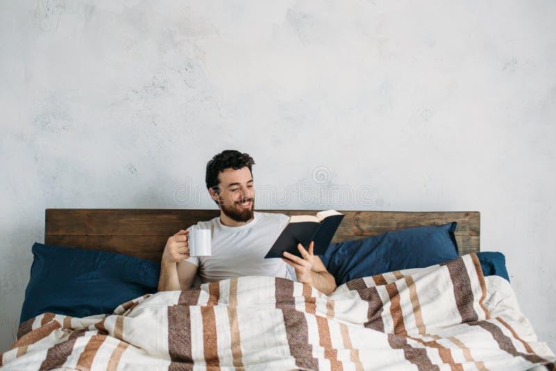 Uomo barbuto che legge un grande libro che si trova nella sua camera da letto fotografie stock libere da diritti
