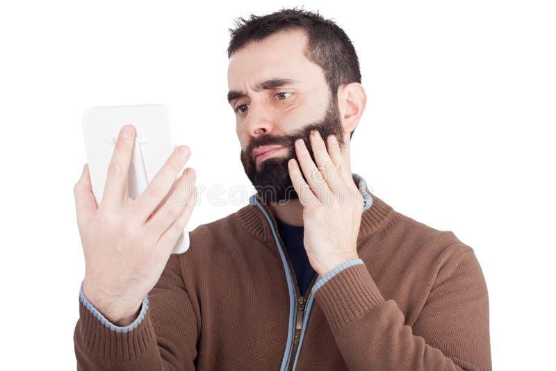 Uomo barbuto che lo esamina specchio disponibile fotografia stock libera da diritti