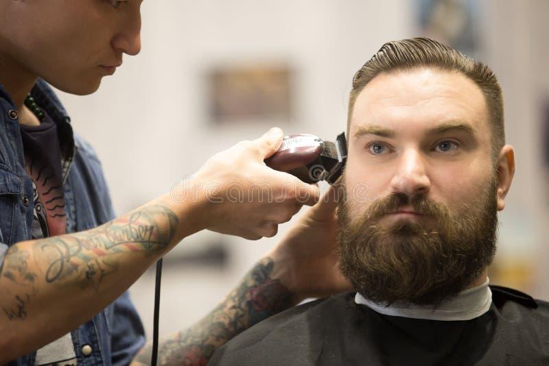 Uomo barbuto che ottiene taglio di capelli in parrucchiere immagini stock libere da diritti