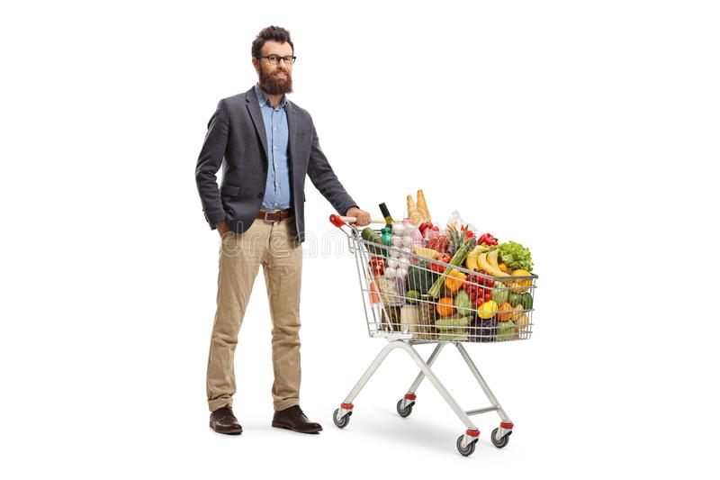 Uomo barbuto che posa con un carrello caricato fotografia stock libera da diritti