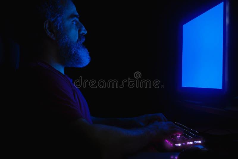 Uomo barbuto che si siede davanti al monitor del computer, mani su una tastiera, funzionante immagini stock