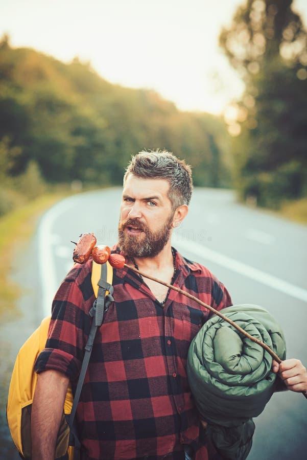 Uomo barbuto con alimento che fa un'escursione sulla strada La viandante dell'uomo mangia la salsiccia sul bastone Pantaloni a vi fotografie stock