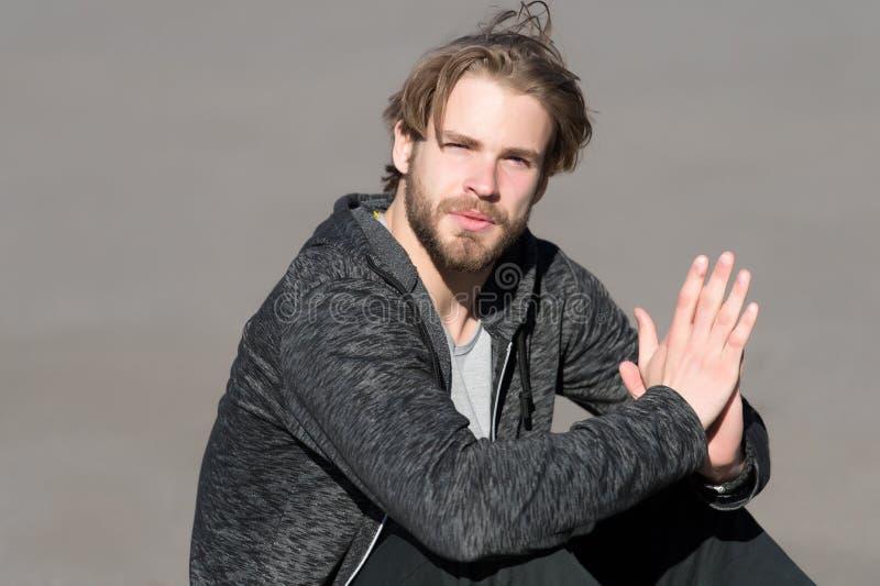 Uomo barbuto con capelli biondi lunghi all'aperto Macho con la barba in abiti sportivi casuali il giorno soleggiato Tipo di modo  fotografie stock