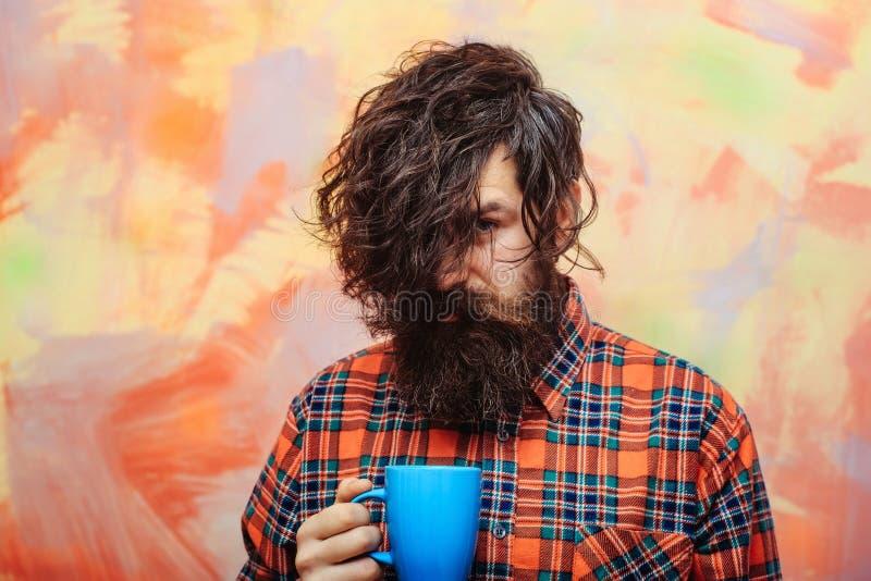 Uomo barbuto con i capelli alla moda della frangia che tengono tazza blu immagine stock libera da diritti