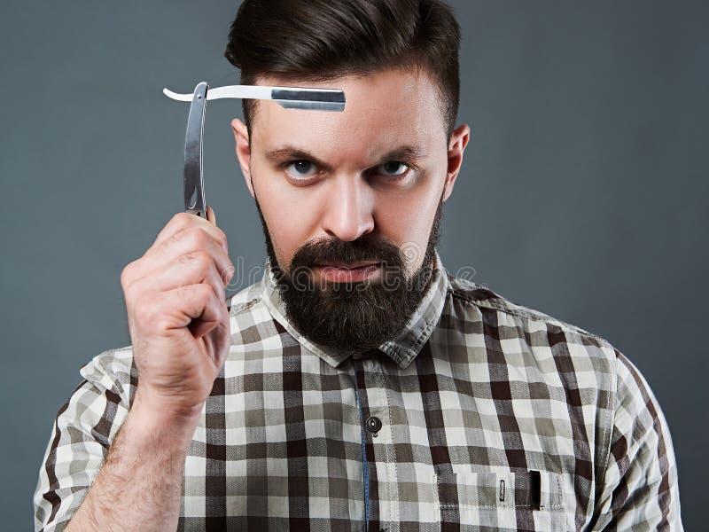 Uomo barbuto con il rasoio diritto fotografia stock