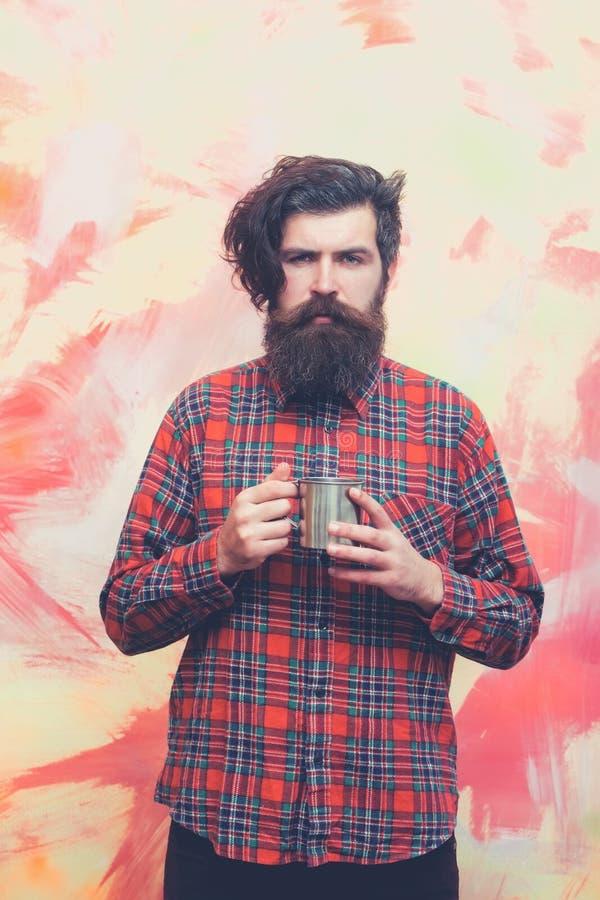 Uomo barbuto con la tazza alla moda del metallo della tenuta dei capelli della frangia immagine stock