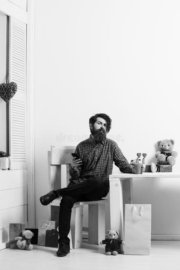Uomo barbuto con lo smartphone e la tazza che si siedono sulla sedia fotografia stock