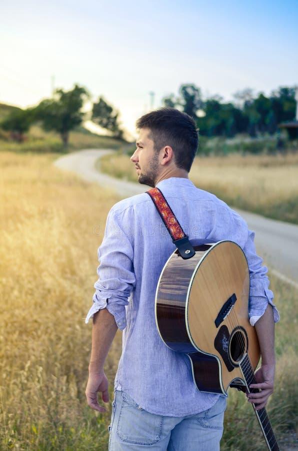 Uomo barbuto con una chitarra fotografia stock libera da diritti