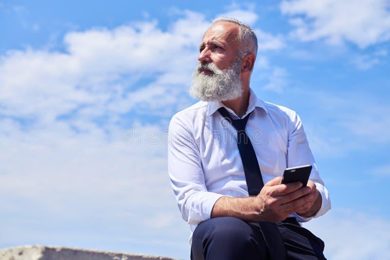 Uomo barbuto contro cielo blu fotografia stock libera da diritti