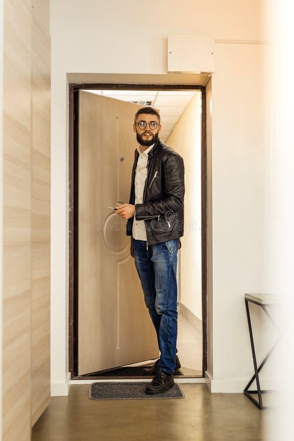 Uomo barbuto dai capelli corti bello che entra nella stanza immagine stock