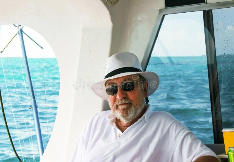 Uomo barbuto dai capelli grigio con il cappello che si rilassa sulla barca della pesca di altura con l'oceano nei precedenti immagini stock
