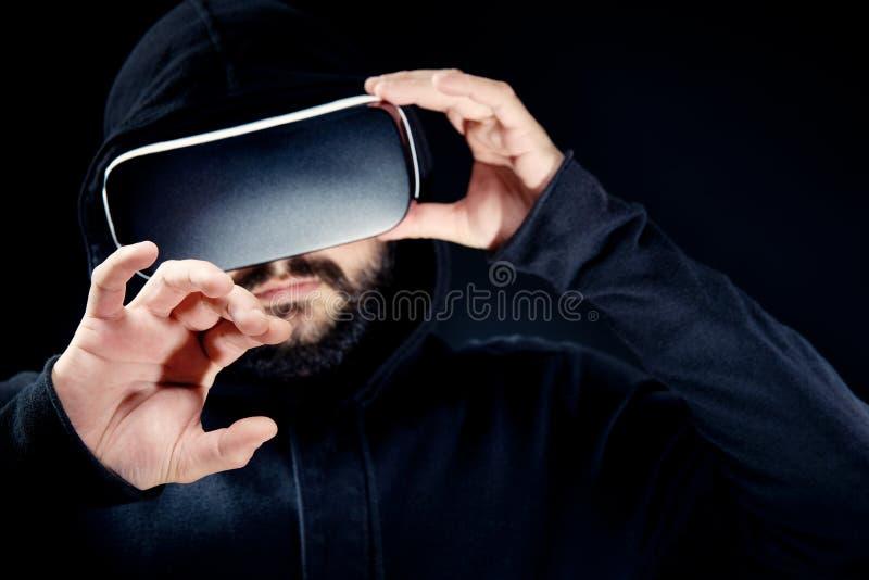 Uomo barbuto dei giovani pantaloni a vita bassa in cima incappucciata nera, occhiali di protezione d'uso di realtà virtuale fotografie stock