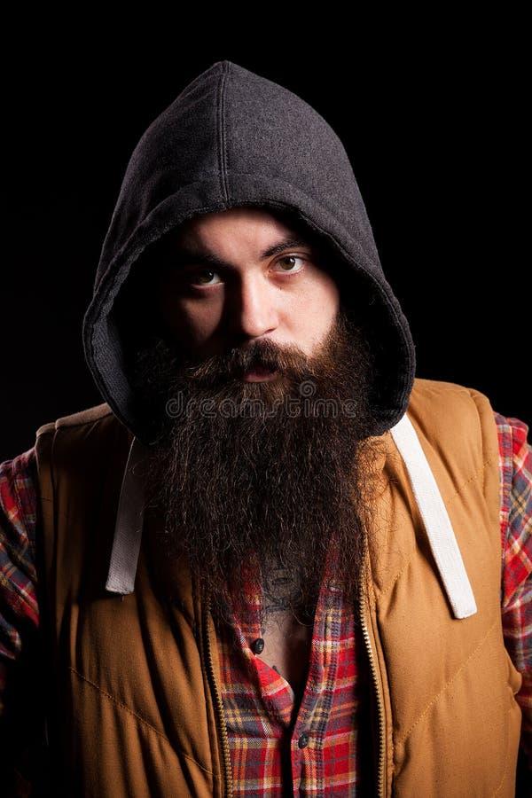 Uomo barbuto dei pantaloni a vita bassa che indossa un cappuccio immagine stock