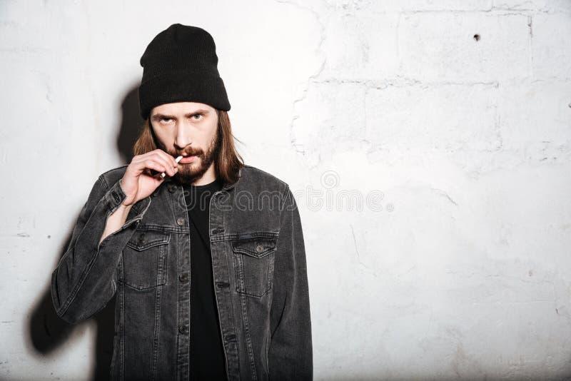 Uomo barbuto dei pantaloni a vita bassa che sta con la sigaretta fotografia stock