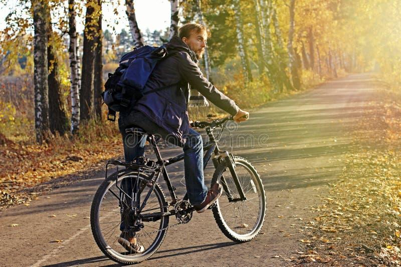 Uomo barbuto dei pantaloni a vita bassa nell'abbigliamento casual con lo zaino e la bicicletta nel parco o nella foresta di autun fotografie stock
