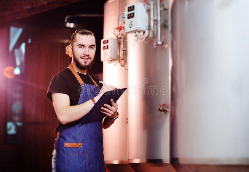 Uomo barbuto del fabbricante di birra su un fondo dei carri armati della birra e una fabbrica di birra che fa le note in una comp fotografie stock