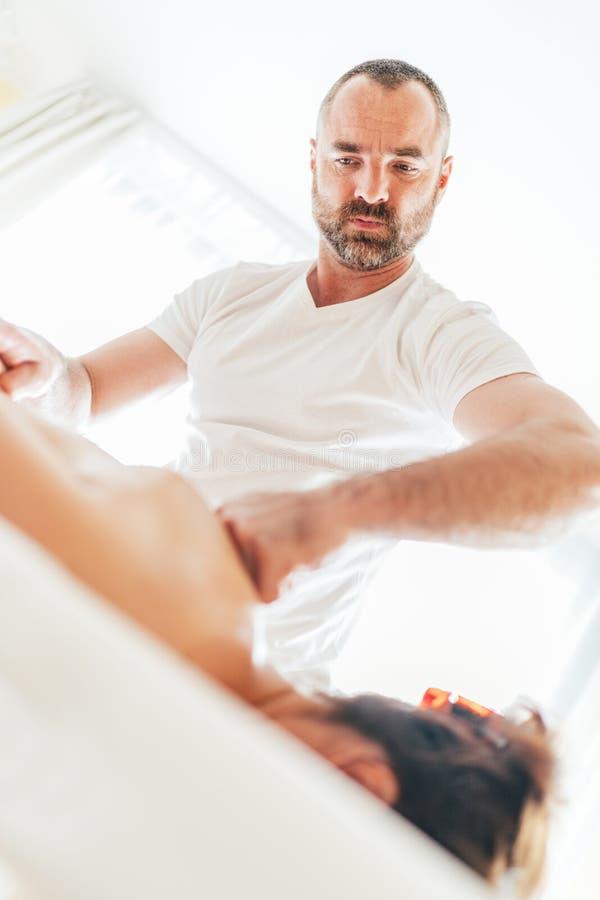 Uomo barbuto del massaggiatore che fa le manipolazioni di massaggio sulla zona di area della scapola durante il giovane massaggio immagine stock