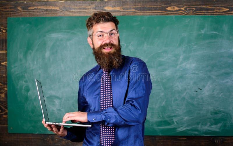 Uomo barbuto dell'insegnante con il fondo moderno della lavagna del computer portatile Formazione in linea Istruzione di tecnolog fotografie stock