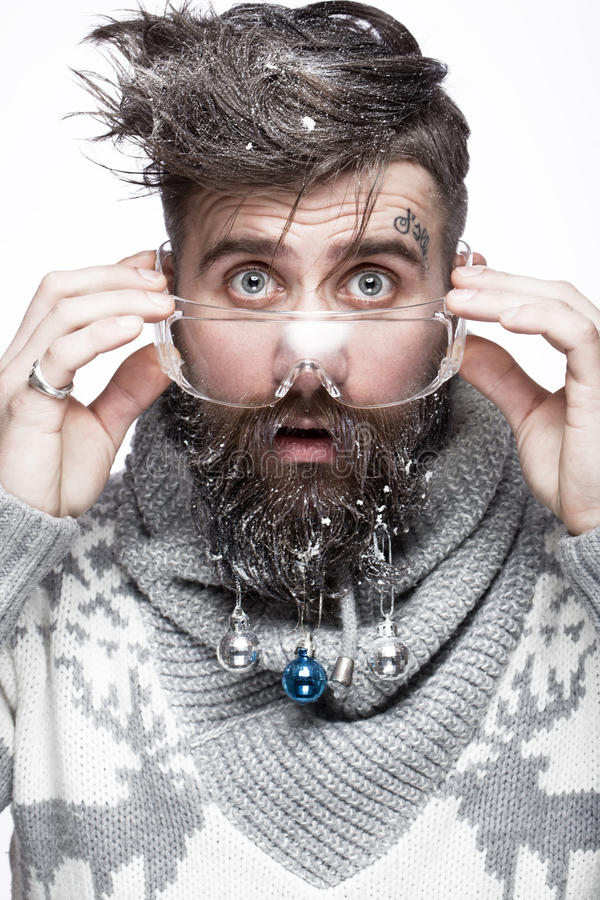 Uomo barbuto divertente in un'immagine del ` s del nuovo anno con neve e le decorazioni sulla sua barba Festività del Natale fotografie stock libere da diritti