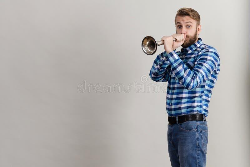 Uomo barbuto divertente in una camicia di plaid che soffia nel corno di rame fotografia stock