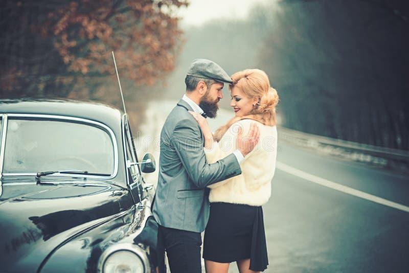 Uomo barbuto e donna sexy in pelliccia Viaggio e viaggio di affari o escursione del legamento Retro automobile della raccolta e r fotografie stock