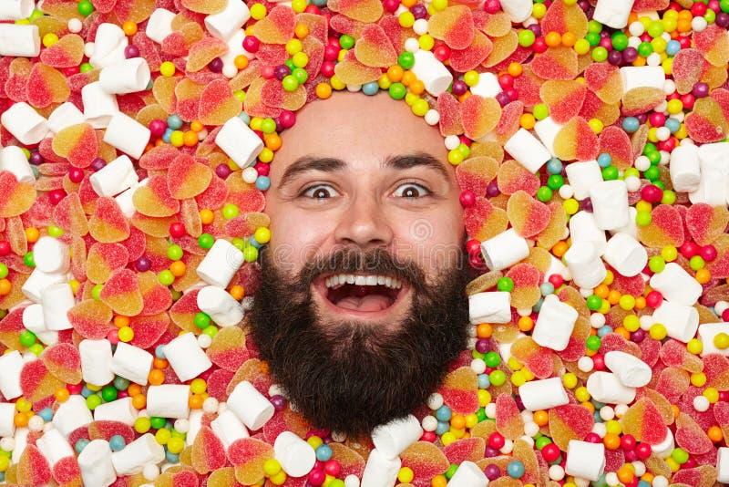 Uomo barbuto emozionante nell'assortimento dei dolci immagine stock