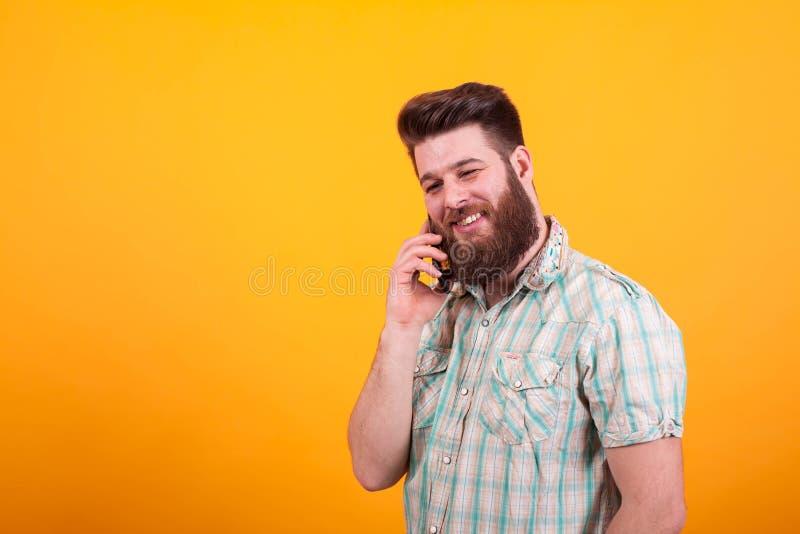 Uomo barbuto felice che ha una conversazione sul suo telefono sopra fondo giallo fotografie stock libere da diritti