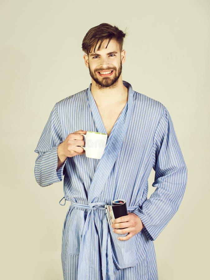 Uomo barbuto felice che sorride in abito con la tazza e la rivista fotografia stock libera da diritti