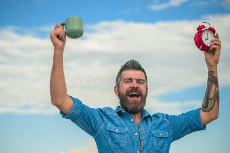 Uomo barbuto felice con l'orologio ed il caffè caffè maturo della bevanda dei pantaloni a vita bassa In pieno di energia Maschio  fotografie stock
