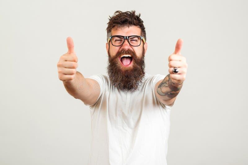 Uomo barbuto fortunato dei pantaloni a vita bassa sopra fondo bianco Vetri d'uso dell'uomo barbuto Vincitore felice Tipo barbuto  immagini stock libere da diritti