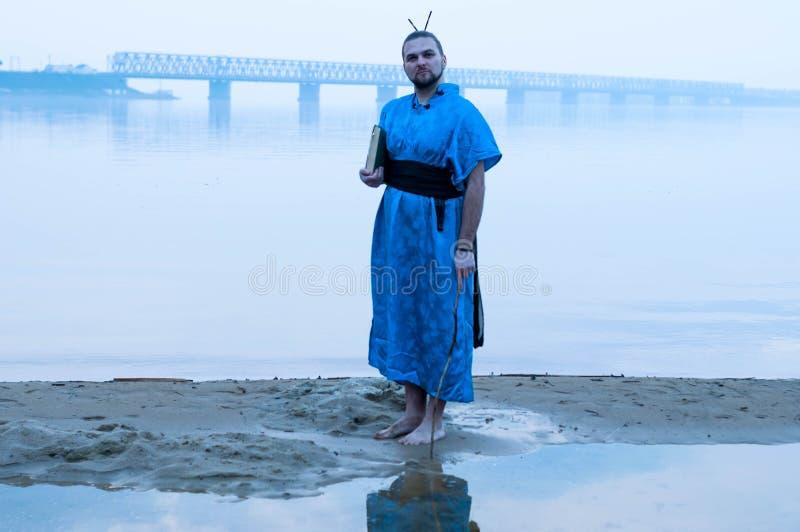 Uomo barbuto in libro blu della tenuta del kimono sulla sponda del fiume in nebbia ed esaminare macchina fotografica immagine stock