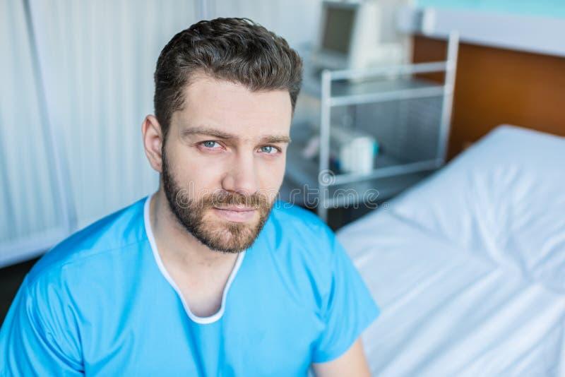 Uomo barbuto malato che si siede sul letto di ospedale e che esamina macchina fotografica immagini stock