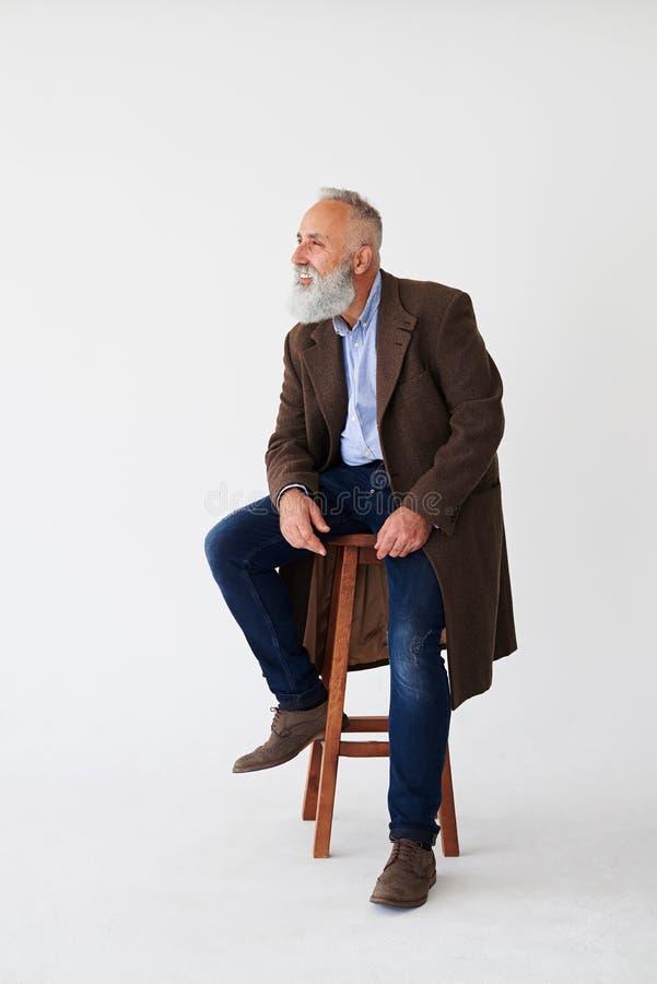Uomo barbuto maturo schietto in cappotto che si siede sulla sedia in studio immagini stock libere da diritti