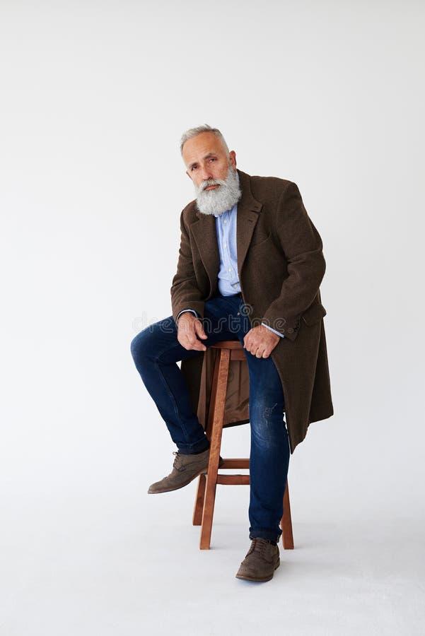 Uomo barbuto maturo serio in cappotto che si siede sulla sedia in studio fotografia stock
