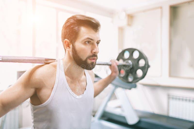 Uomo barbuto muscolare durante l'allenamento nella palestra Culturista che fa sollevamento pesi Chiuda su di giovane femmina atle fotografia stock